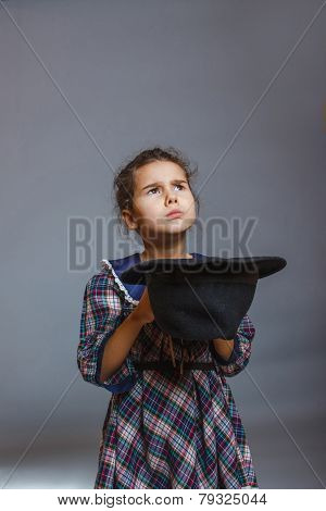 girl child beggar holding hat just money on a gray background