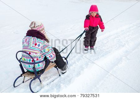 Little Baby Girl In Pink Pulling A Sled With Her Big Sister On Snowy Winter Road