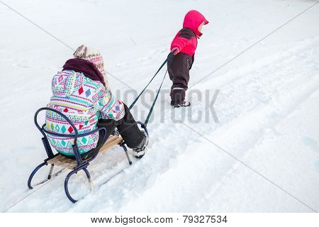 Little Baby Girl In Pink Pulling A Sled With Her Big Sister On Snowy Road