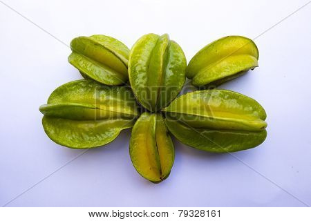 closeup of a half ripen starfruit on a solid background