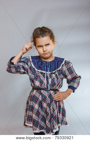 girl on gray background a dress deep in thought