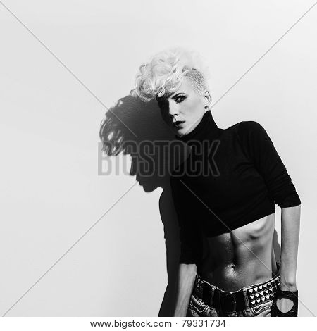 Blond Model On Wall Background With Shadow. Stylish Haircut. Punk Style