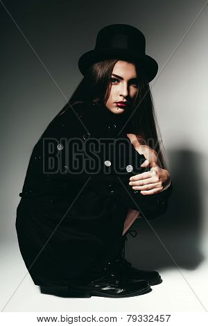 Woman Sitting In Black Dress And Hat