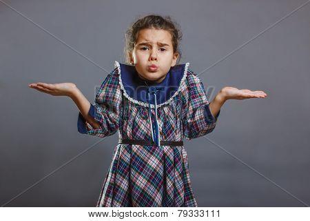 girl spread her hands in disbelief on gray background