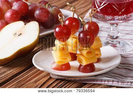 Red Grapes And Cheese On Skewers And A Glass Of Wine Close-up