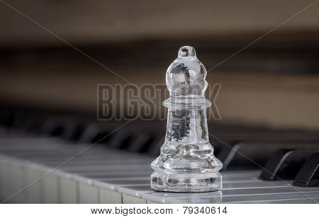 Glass chess bishop on the piano (shiny)