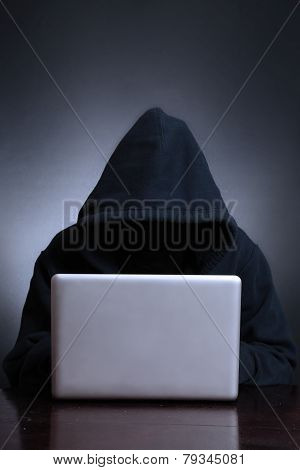 Silhouette of a hacker looking in monitor