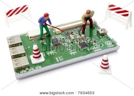 Miniature Toy Workers Repairing Computer Part With Circuit