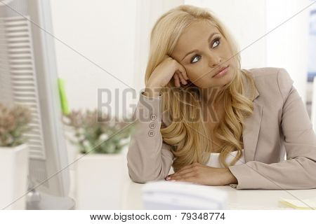 Beautiful blonde businesswoman sitting bored at desk, daydreaming.