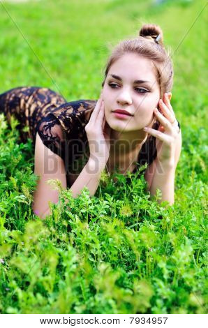 Girl Laying In Bright Green Grass
