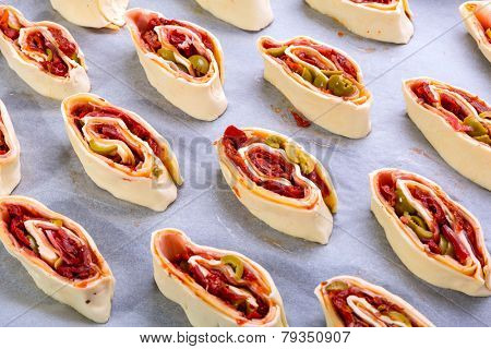 Swiss roll pastry stuffed with ham, olives and sundried tomatoes ready for cooking