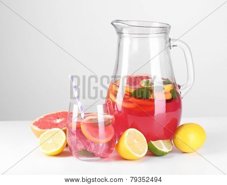 Pink lemonade in glass and pitcher isolated on white