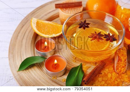 Spa still life with candle light on wooden plate, on color wooden background