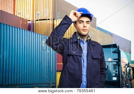 Worker holding his helmet in front of a stack of containers
