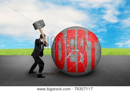 Businessman Holding Hammer Hitting Cracked Debt Ball With Sky Clouds