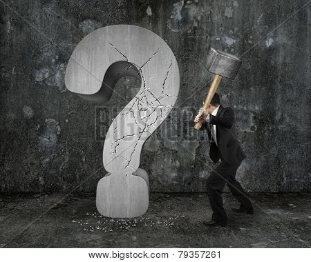 Businessman Holding Hammer Cracked Question Mark With Dark Mottled Wall