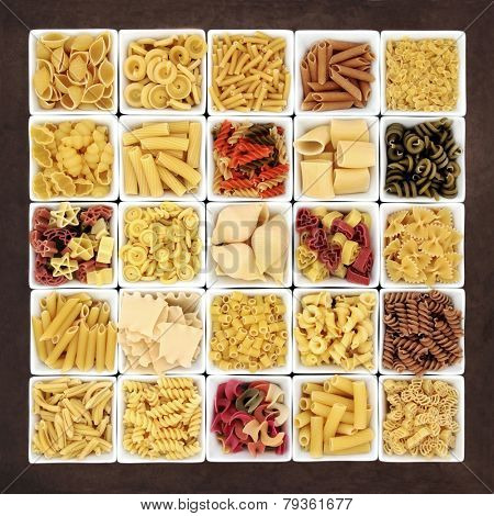 Large pasta dried food sampler in square dishes over brown lokta paper background.
