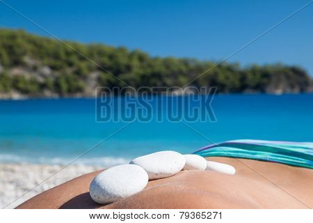 Beautiful woman getting hot stones treatment out in the nature.
