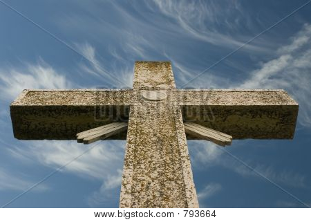 Weathered cross blue sky and wispy clouds