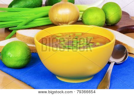 Bowl of onion soup with spring onion on a table