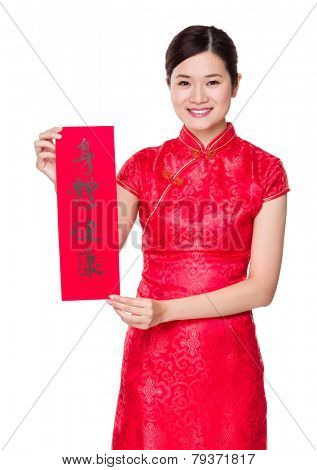 Woman with traditional cheongsam and holding Fai Chun, phrase meaning is blessing for good health