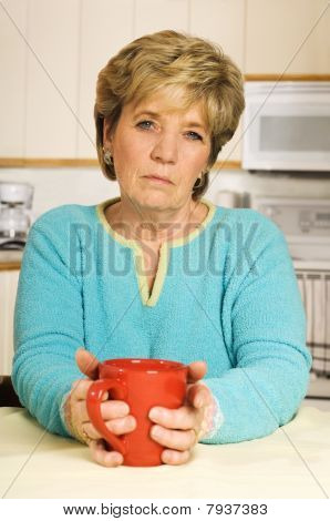 Senior Woman, Looking Unhappy, Holds A Coffee Mug