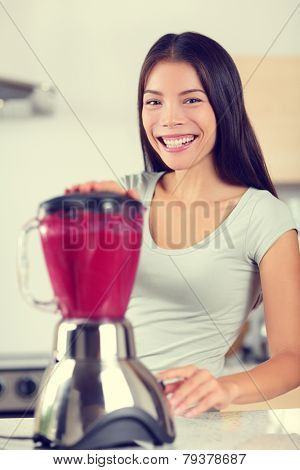 Berry smoothie woman making fruit breakfast smoothies with blender. Healthy eating lifestyle concept portrait of beautiful young woman preparing drink blending strawberries, raspberries and berries.