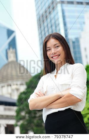 Business woman smiling portrait in Hong Kong. Businesswoman standing happy and successful in suit cross-armed. Young multiracial Chinese Asian / Caucasian female professional in central Hong Kong.