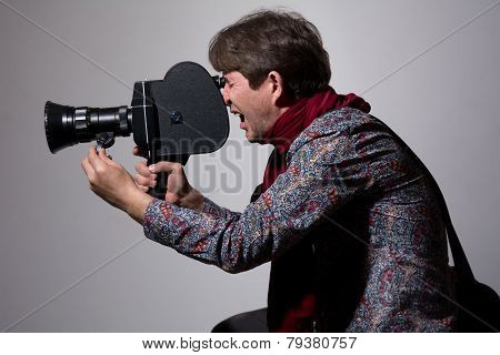 A Man With An Old Movie Camera On A Gray Background.