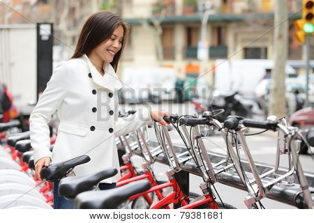 City bike - woman using public city bicycles sharing system. Biking female professional parking city bikes after cycling on city bicycle. Barcelona, Spain, Europe.
