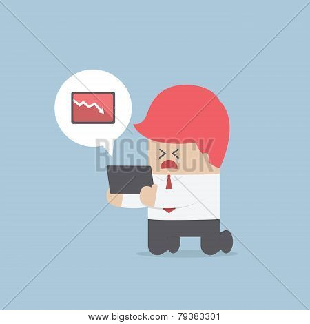 Businessman Holding A Tablet With Falling Profits Graph