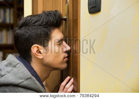 Young Man Spying Through The Keyhole Of A Door