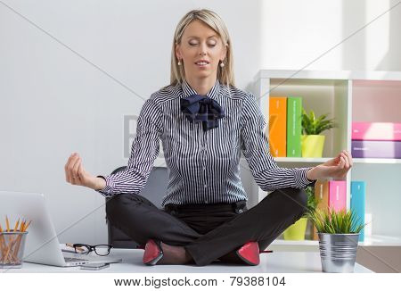 Woman sitting in lotus yoga pose in office
