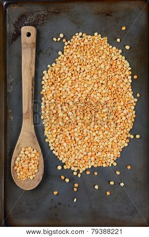 High angle shot of yellow split peas and a wooden spoon on a used metal baking sheet. Vertical Format.