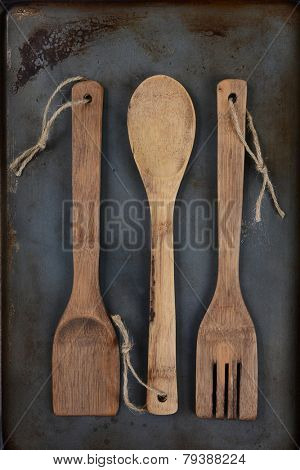Overhead shot of wooden kitchen utensils, fork, spoon, and spatula, with twine through the handle hole on a used metal baking sheet. Vertical Format with middle spoon inverted..