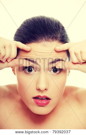 Woman checking her wrinkles on her forehead .