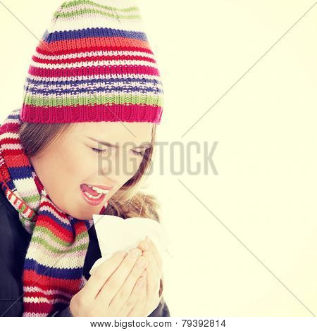 Sneezing woman with handkerchief, close up.