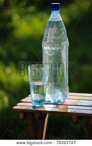 Glass Of Water And Bottle With Mineral Water On Nature Background