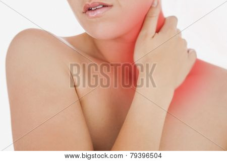 Topless woman massaging neck over white background