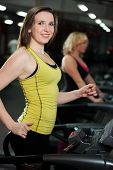 stock photo of cardio exercise  - Smiling sporty girl exercising on cardio trainer treadmill in gym