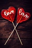 stock photo of lolli  - Couple of heart shape lolly pops on wooden background - JPG
