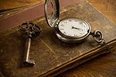 stock photo of vintage jewelry  - Vintage pocket watch old book and a brass key on a vintage surface - JPG