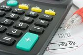 picture of statements  - a close up of a calculator and red pen sitting on a bank statement - JPG