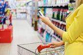 stock photo of grocery cart  - Woman checking shopping list on her smartphone at supermarket - JPG