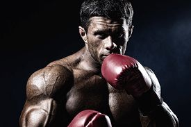 stock photo of boxers  - Strong muscular boxer in red boxing gloves - JPG