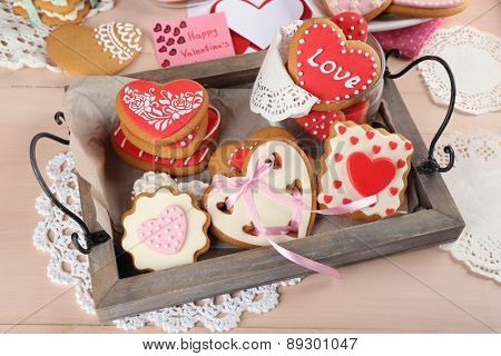 Heart shaped cookies for valentines day on tray, on color wooden background