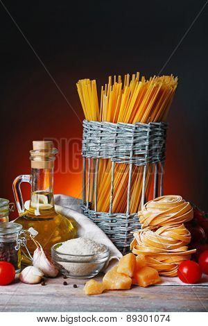 Pasta with cherry tomatoes and other ingredients on dark background