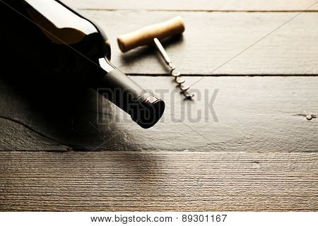 Glass bottle of wine with corkscrew on wooden table background