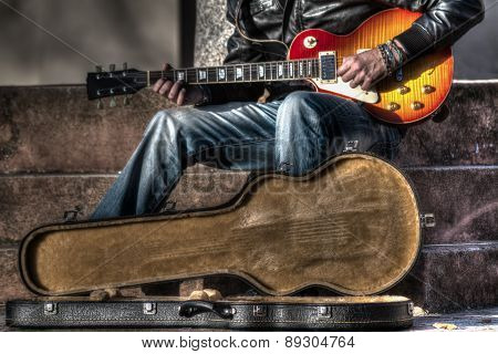 Guitar Player With An Open Guitar Case