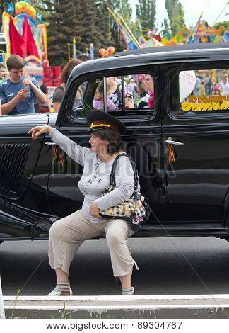 Makeevka, Ukraine - May, 9, 2012: Woman In A General's Cap Near The Retro Car During The Celebration